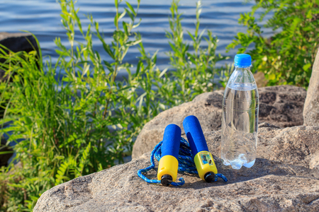 saltar: Jump rope and bottle with water on rock with river embankment background. Summer, active lifestyle