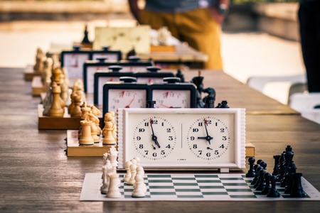 Variety of chess boards with chess pieces and chess clocks on wooden desk in due to the chess tournament. Selective focus on first chess clock. Outdoors chess competition