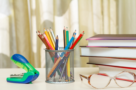 School supplies. Books, colour pencils, glasses, stapler on wooden table. Back to school concept.