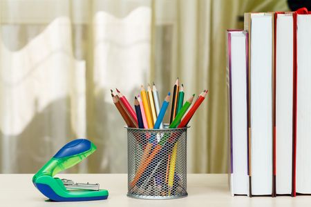 School supplies. Books, colour pencils, stapler on wooden table. Back to school concept.