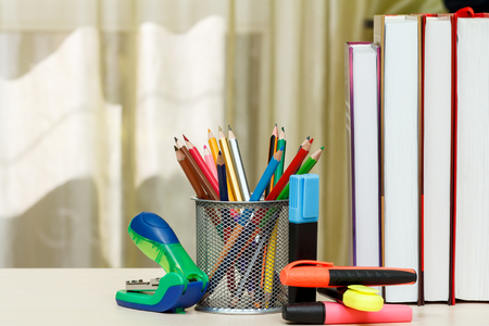 School supplies. Books, colour pencils, markers, stapler on wooden table. Back to school concept.