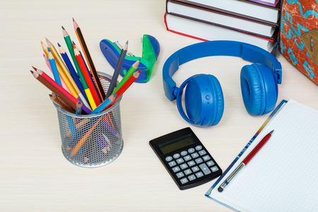 School supplies. School backpack, books, metal stand for pencils with color pencils, stapler, headphones, calculator and notebook with pen on wooden table. Top view. Back to school concept.