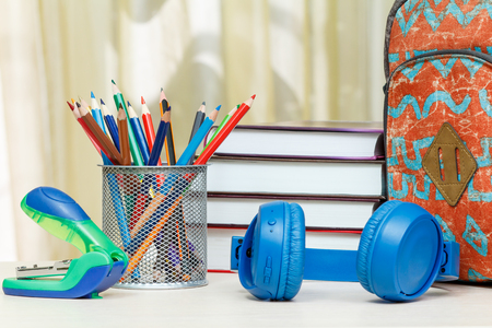 School backpack with school supplies. Books, metal stand for pencils with color pencils, stapler and headphones on wooden table. Back to school concept. Stock Photo