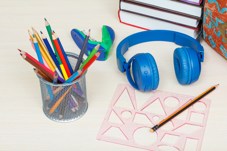 School supplies. School backpack, books, metal stand for pencils with color pencils, stapler, headphones and plastic ruler on wooden table. Top view. Back to school concept.