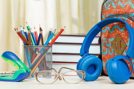 engrapadora: School backpack with school supplies. Books, metal stand for pencils with color pencils, stapler, glasses and headphones on wooden table. Back to school concept.
