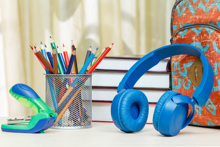 engrapadora: School backpack with school supplies. Books, metal stand for pencils with color pencils, stapler and headphones on wooden table. Back to school concept. Foto de archivo