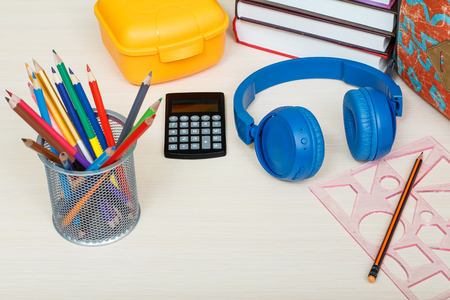 engrapadora: School supplies. School backpack, books, yellow sandwich box, metal stand for pencils with color pencils, stapler, headphones, calculator and ruler with pencil on wooden table. Top view. Back to school concept.