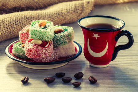 Cup of coffee with coffee beans and Turkish delight lying on saucer on wooden board with piece of sackcloth