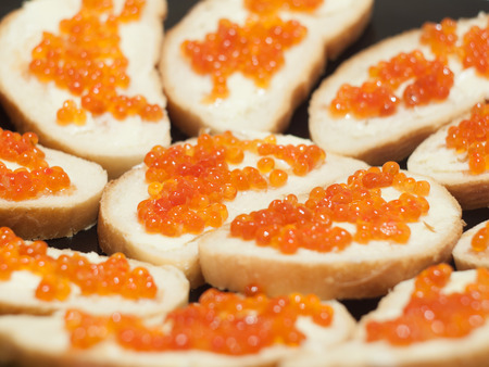 Sandwiches with butter and red caviar. Selective focus on the center.