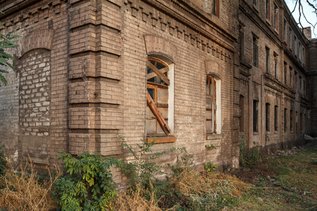 windows frame: Facade of old abandoned brick building with window lined with wooden boards