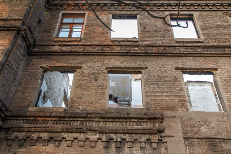 windows frame: Facade of old abandoned brick building with empty window openings except one Stock Photo