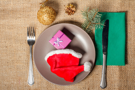 Christmas red hat and present in gift box on plate, fork and knife on green napkin, cone, glittering ball and natural fir tree branch on sackcloth. Christmas and New Year table setting
