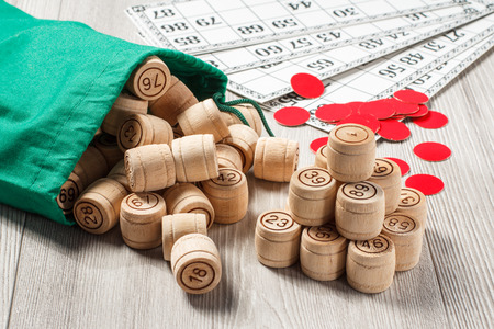 Board game lotto. Stacked wooden lotto barrels with bag, game cards and red chips for a game in lotto on the background Foto de archivo
