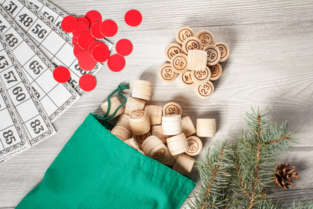 Board game lotto. Wooden lotto barrels with bag and game cards for a game in lotto, Christmas fir tree branches and cone. Top view