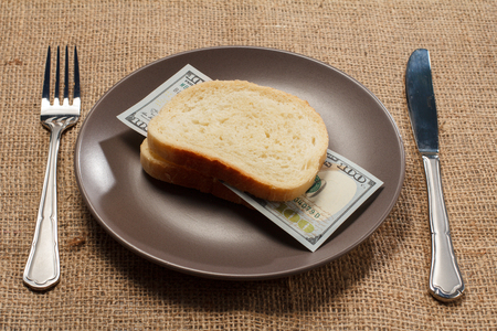 Two slices of bread with one hundred American dollars bill as hamburger of money on brown plate with fork and knife. Money ready to be eaten. Concept of financial relationships