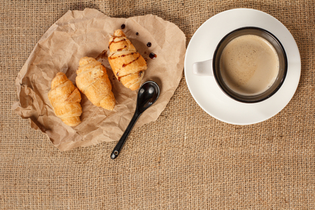 Cup of black coffee with saucer on sackcloth, fresh croissants with chocolate on wrapping paper. Top view