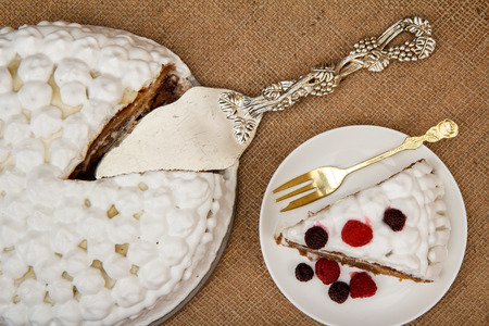 Sliced biscuit cake decorated with whipped cream and raspberries, silver cake lifter beside it on table with sackcloth. Top view