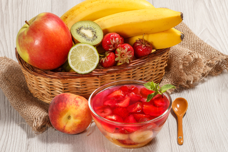 Cherry jelly with strawberry pieces in the glass bowl topped mint leaves, fresh strawberries, nectarine, lime, kiwi, banana, apple in a wicker basket on a wooden table Standard-Bild