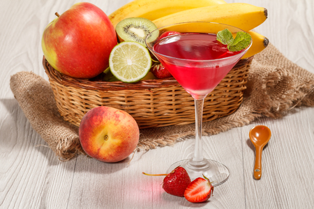 Cherry jelly in the glass topped mint leaves, fresh strawberries, nectarine, lime, kiwi, banana, apple in a wicker basket on a wooden table Standard-Bild