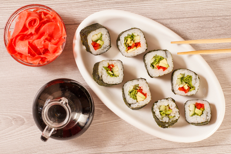 Sushi rolls with rice, pieces of avocado, cucumber, red bell pepper and lettuce leaves on ceramic plate, chopsticks, glass bottle with soy sauce and pickled ginger in a bowl. Top view Stock Photo