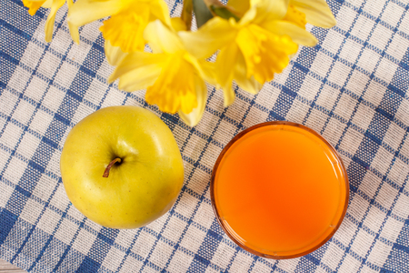 Good and delicious food and beverages for breakfast. Green apple, yellow daffodils and glass of orange juice on kitchen napkin. Top view Stock Photo
