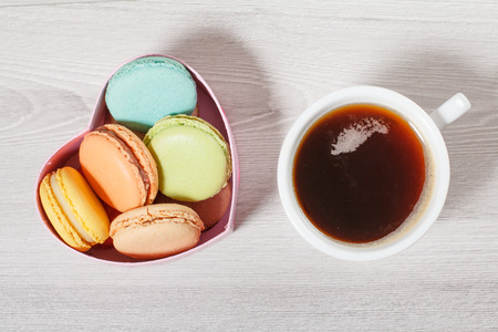 Tasty macaroons cakes of different color in cardboard box in the shape of heart and cup of coffee on gray boards. Top view Stock Photo