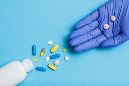 Close up white bottle with different pills and capsules and hand of female doctor in blue latex glove with pills on the palm. Legal drug store concept