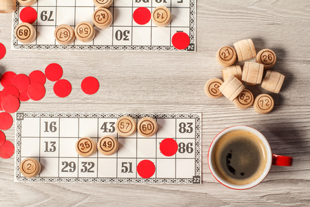 Board game lotto. Wooden lotto barrels, game cards, red chips and cup of coffee. Top view