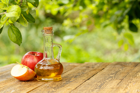 Apple vinegar in glass bottle with cork and fresh red apples on old wooden boards with blurred green natural background