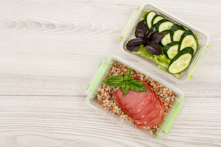 Plastic meal prep containers with boiled buckwheat porridge and slices of meat, fresh cucumbers and salad on grey wooden background. Top view with copy space