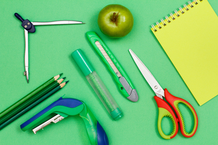 Color pencils, compass, stapler, felt-tip pen, paper knife, apple, scissors and notebook on green background. Top view. Back to school concept. School supplies