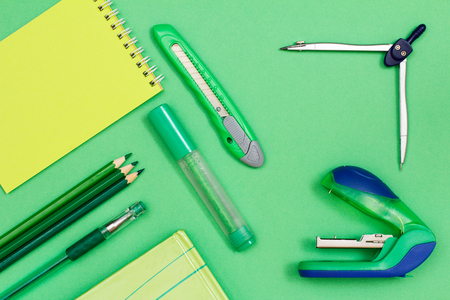 Notebook, color pencils, pen, book, felt-tip pen, paper knife, compass and stapler on green background. Top view. Back to school concept. School supplies