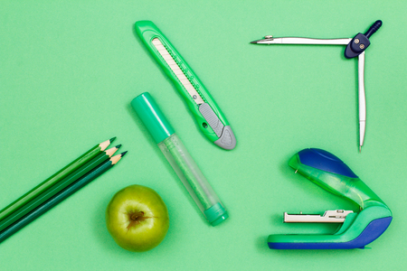 Color pencils, apple, felt-tip pen, paper knife, compass and stapler on green background Stock Photo