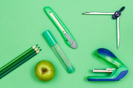 Color pencils, apple, felt-tip pen, paper knife, compass and stapler on green background 版權商用圖片