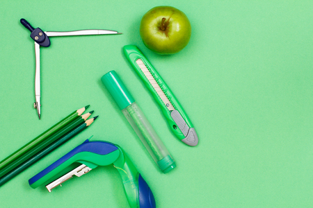 Color pencils, compass, felt-tip pen, paper knife, stapler and apple on green background Stock Photo