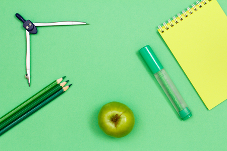 Color pencils, compass, apple, felt-tip pen and notebook on green background