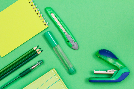 Notebook, color pencils, pen, book, felt-tip pen, paper knife and stapler on green background. Top view. Back to school concept. School supplies