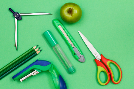 Color pencils, compass, stapler, felt pen, paper knife, apple and scissors on green background. Top view. Back to school concept. School supplies