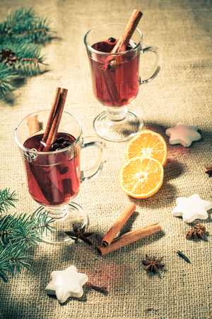 Glass of Christmas mulled wine with cinnamon, star anise and cloves on sackcloth with white biscuits, slices of orange, natural fir tree branches and cones. Color toning effect.