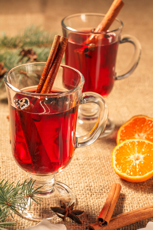 Glass of Christmas mulled wine with cinnamon, star anise and cloves on sackcloth with slices of orange, natural fir tree branches and cones. Color toning effect. Standard-Bild
