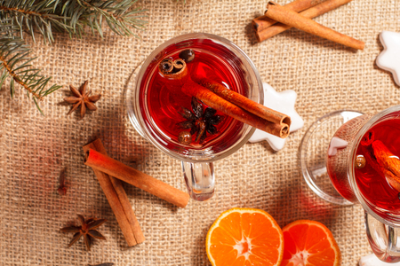 Glass of Christmas mulled wine with cinnamon, star anise and cloves on sackcloth with white biscuits, slices of orange, natural fir tree branches and cones. Top view. Color toning effect.