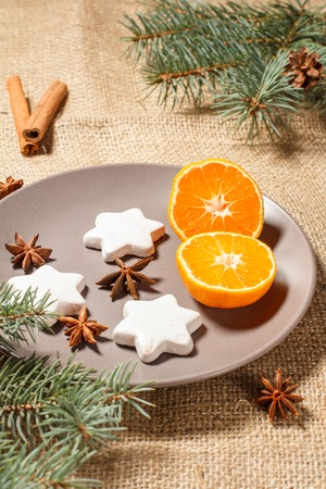 Gingerbread cookies in star shape on plate with cinnamon, star anise and natural fir tree branches with cones on sackcloth. Color toning effect.