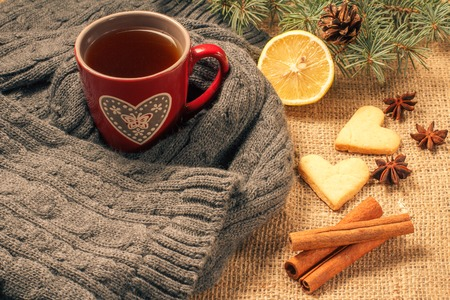 Red cup of tea wrapped up in wool scarf, slice of lemon, natural fir tree branches with cone, star anise, cinnamon and gingerbread cookies in heart shape on sackcloth. Color toning effect. Stock Photo