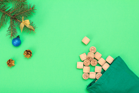 Board game lotto. Wooden lotto barrels with bag, Christmas fir tree branches, cones and toy ball on green background. Top view