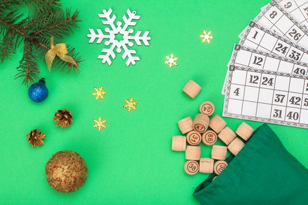 Board game lotto. Wooden lotto barrels with bag and game cards for a game in lotto, Christmas fir tree branches, cones, decotative snowflackes and toy balls on green background. Top view