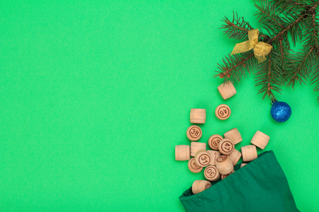 Board game lotto. Wooden lotto barrels with bag, Christmas fir tree branch and toy ball on green