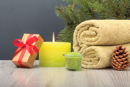 Spa composition with gift box and cone. Soft terry towel, bowl with sea salt, burning candle and natural fir tree branch on gray