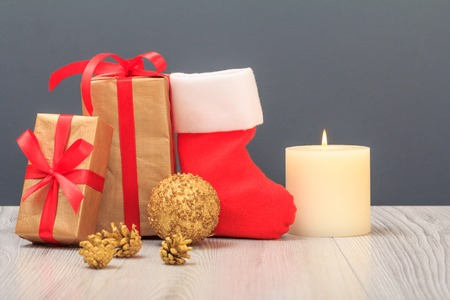 Christmas decoration. Gift boxes, Santa's boot, toy ball, cones and burning candle on gray