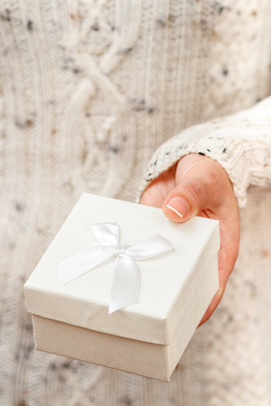 Woman holding a gift box in her hand. Shallow depth of field, Selective focus on the box. Concept of giving a gift on holiday or birthday. Stock Photo
