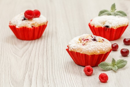 Homemade fruit muffins sprinkled with powdered sugar and fresh raspberries on wooden desk. Christmas sweets and pastries. Standard-Bild